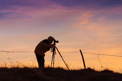 Silhouette of photographer with photo camera. On a tripod against the majestic sky in a pink light of sunrise stock photography