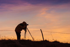 Silhouette of photographer. With photo camera on a tripod against the majestic sky in a pink light of sunrise royalty free stock photo