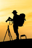 Silhouette of photographer shooting for a sunrise. On the orange sky Stock Photos