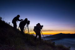 Silhouette of a photographer standing on mountain Stock Image