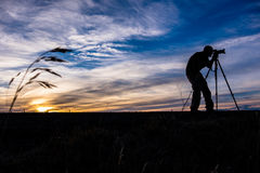Silhouette of a Photographer at Sunrise in the Country Royalty Free Stock Images