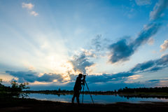 Silhouette photographer on sunset background Stock Photos