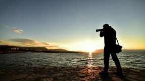 Photographer on the sea shore. Silhouette of photographer at sunset holding a camera with long lens pointing it at the sea probably catching a dolphin or other Royalty Free Stock Photos
