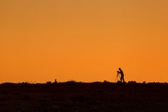Silhouette of photographer during sunset with tripod Stock Photos