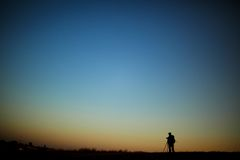 Silhouette of a photographer during the sunset. Silhouette of a young photographer during the sunset Royalty Free Stock Image