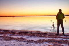 Silhouette of  photographer take photo of fall offshore with beautiful sunset sky royalty free stock photos