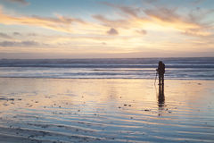 Silhouette of photographer taking a magnificent sunrise on the seashore Stock Image