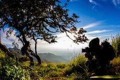 Silhouette of photographer taking photo on bright orange sunset. Royalty Free Stock Photo