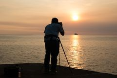 Silhouette photographer taking photo of ocean at and sunset. With fishing boat Royalty Free Stock Image