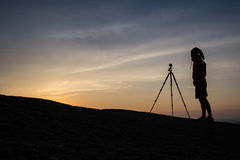 Silhouette of photographer taking photo in sunset Stock Photography
