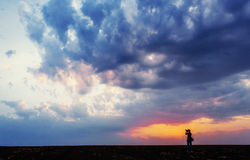 Silhouette of photographer taking photo at sunset Royalty Free Stock Images