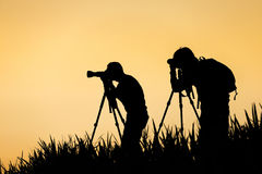 Silhouette of photographer taking photo. At sunset Stock Photos