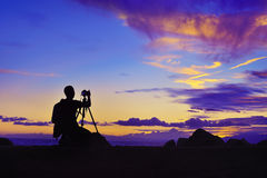 Silhouette of photographer taking photo at sunset beside the sea Royalty Free Stock Photography