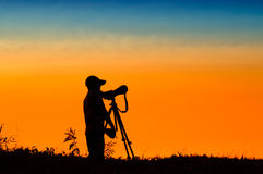 Silhouette of photographer taking picture of landscape during su Stock Photo