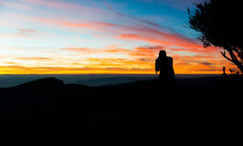 Silhouette of photographer taking picture of landscape during su Royalty Free Stock Images