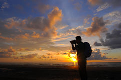 Silhouette a photographer taking pictures of sunrise on a rock,. Near the tropical beach, Malaysia Stock Photo