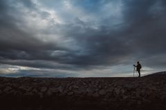 Silhouette of a photographer or traveler with tripod standing on stone. Background of a dramatic sky. Hazardous working stock photos