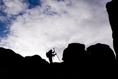 Silhouette of the photographer with tripod against the sky Stock Photography