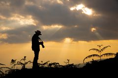 Silhouette of a photographer who shoots a sunset stock image