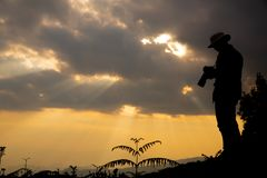 Silhouette of a photographer who shoots a sunset royalty free stock images