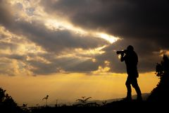 Silhouette of a photographer who shoots a sunset royalty free stock photography
