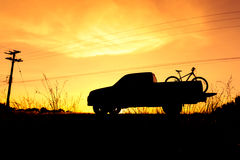 Silhouette Pickup truck with bicycle. At sunset sky Stock Images