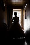 Silhouette  picture of the bride. The bride goes on a dark corridor. silhouette photo Stock Images