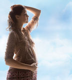 Silhouette picture of pregnant beautiful woman. Family, motherhood and pregnancy concept - silhouette backlight picture of pregnant beautiful woman touching her stock images