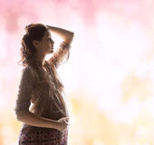 Silhouette picture of pregnant beautiful woman. Family, motherhood and pregnancy concept - silhouette backlight picture of pregnant beautiful woman touching her royalty free stock photo