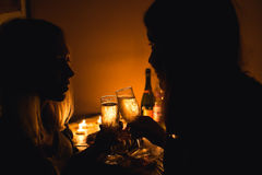 Silhouette picture of two girls clink glasses with champagne. Candle light.  Royalty Free Stock Photography