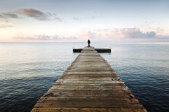 Silhouette on a pier. Lonely silhouette standing on an empty wooden pier in the morning with beautiful clouds and azure sky Stock Photos