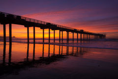 Silhouette pier at beach and brilliant sunset Stock Image