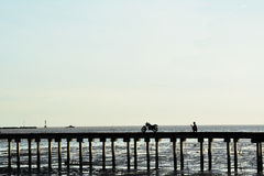 Silhouette pier. With men and motorcycle Stock Images