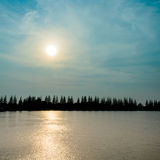 Silhouette Pine Tree and Reflection Sunbeam on River Royalty Free Stock Photography