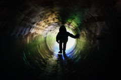 Silhouette in the pipe. Silhouette of a man child in a tube Stock Photography