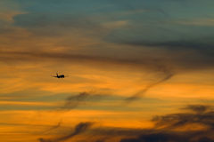 The silhouette of the plane in the evening sky Royalty Free Stock Image