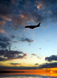 Silhouette of plane fly over sea. royalty free stock photos