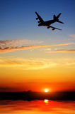 Silhouette of plane fly over water Stock Photo