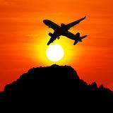 Silhouette plane in the sky in the evening sunset. stock image