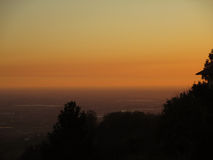 The silhouette of plants against beautiful gradation of pastel yellow and orange of the after sunset sky, Bergamo Royalty Free Stock Photography
