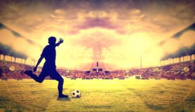 Silhouette of a player shooting football on goal at the football. Stadium on night Stock Photo