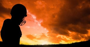 Silhouette player wearing sport helmet against cloudy sky during sunset