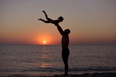 Silhouette of playing dad and daughter on the background of the sea sunset stock photography