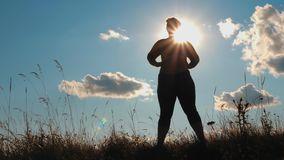 Silhouette plus size girl doing exercises outdoors. Silhouette: young plus size girl doing sport exercises on grass spending time in highlands in the morning stock video footage