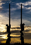 Silhouette pole climbing. Silhouette man climbing a pole racing with the sun on a cloudy scene Stock Photography
