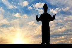 Silhouette of the Pope against the evening sky Royalty Free Stock Image