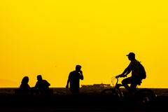Silhouette pople in izmir. Silhouette people in Izmir Turkey. Bicycle riding man, a phone calling man, and two people sitting on a bench near the seaside in Stock Photos