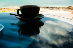 Silhouette porcelain cup and saucer with spoon on background glass table. Reflection sky and clouds on glass top table. Silhouette cup and saucer. Silhouette Stock Photos