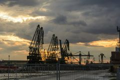 Silhouette of port cranes against a dramatic sky at sunset. royalty free stock photography