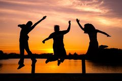 Silhouette portrait group of people jumping with the light of sunset and blue sky in background stock photo